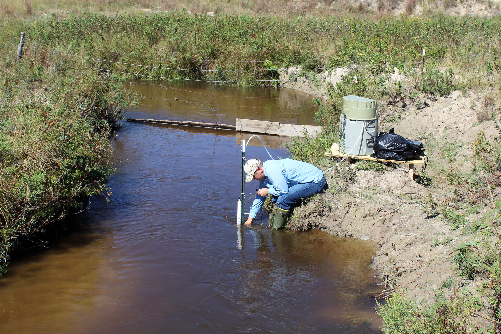 Troy Gilmore sets up to take groundwater samples from the Loup River in the Sandhills of Nebraska in September 2018. By sampling groundwater and determining its age, they hope to determine whether predictions for groundwater discharge rates and contaminat