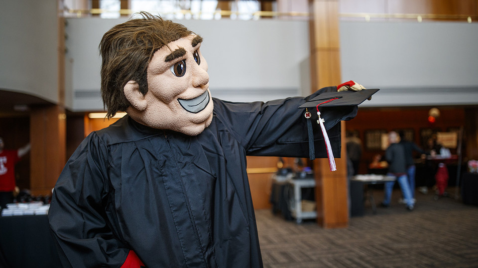 Herbie Husker gets fitted with a commencement gown during Nebraska Gradfest in late November at the Wick Alumni Center. The university's December commencement exercises are Dec. 14 and 15 at Pinnacle Bank Arena. |  Craig Chandler, University Communication
