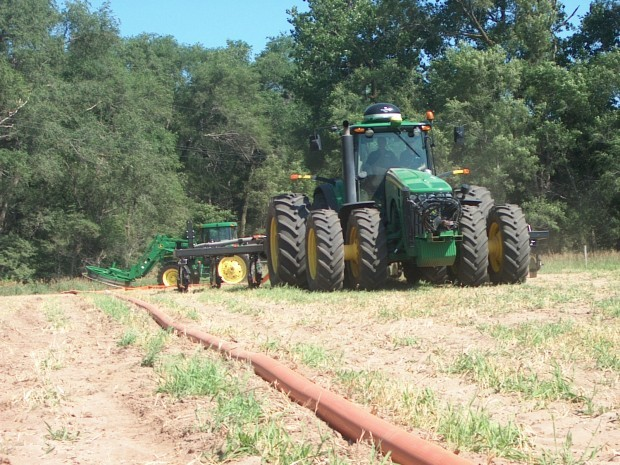 Demonstration of  a system that moves manure from a storage pit through the hose visible near the tractor to the injecting equipment on the back of the tractor. Knifing manure directly into soil minimizes odor and flies. (Photo: Lincoln Journal Star)