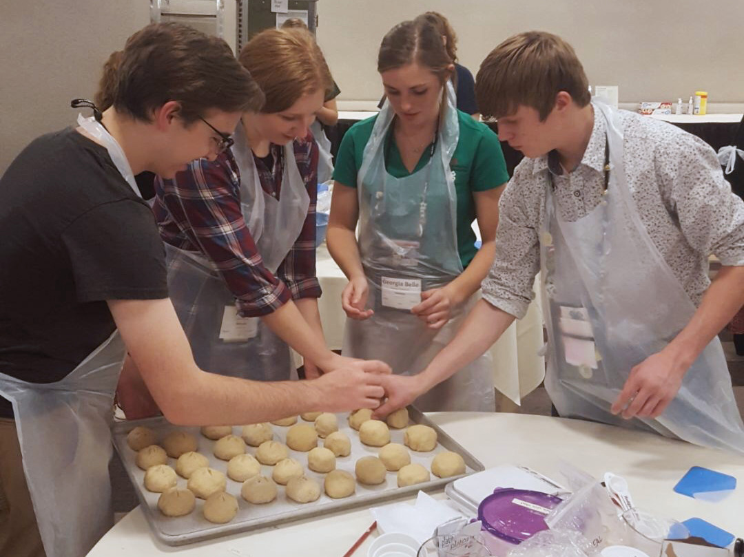 Anna Sump and three other delegates baking bread as part of a workshop. The bread was then donated to the Atlanta Community Food Bank.