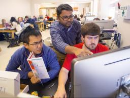 Nebraska researcher Santosh Pitla (center) assists students with a sensor-building project.