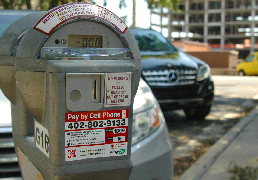 Stickers on parking meters across City and East campuses provide information on how to use the new RingGo pay by cell phone program. The program started in June and is also available at the 17th and R Street parking garage.
