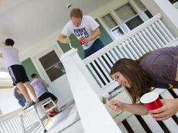 Kate Christensen and Theron Christensen paint porch columns at a house on B Street as part of a citywide Paint-A-Thon Aug. 20, 2016. |  Craig Chandler, University Communication