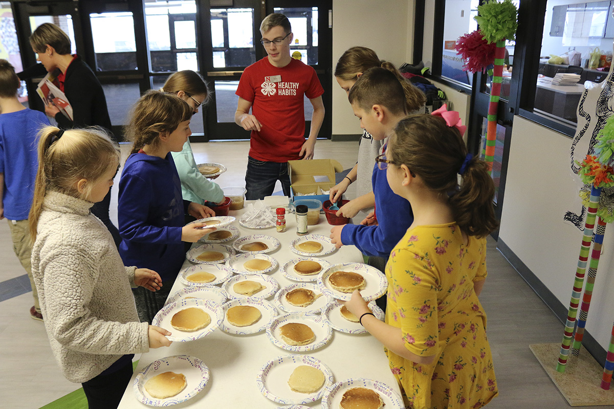 A teen ambassador helps Malcolm fourth-grade students prepare oatmeal pancakes with fruit instead of syrup. (Photo by Vicki Jedlicka, Nebraska Extension in Lancaster County)