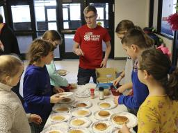 Teen ambassadors help Malcolm fourth-grade students prepare oatmeal pancakes with fruit instead of syrup. (Photo by Vicki Jedlicka, Nebraska Extension in Lancaster County)