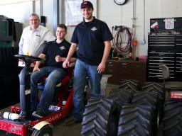 Roger Hoy (from left), Caleb Lindhorst and Luke Prosser show off a tractor designed by students for a 2014 engineering competition. Lindhorst was involved in a December 2013 auto accident and support from Hoy and Prosser has helped him return to classes o