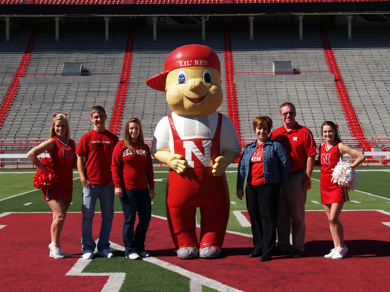 The Berka family strikes a pose with Lil' Red and Husker cheerleaders during their 2010 Parents Week visit.