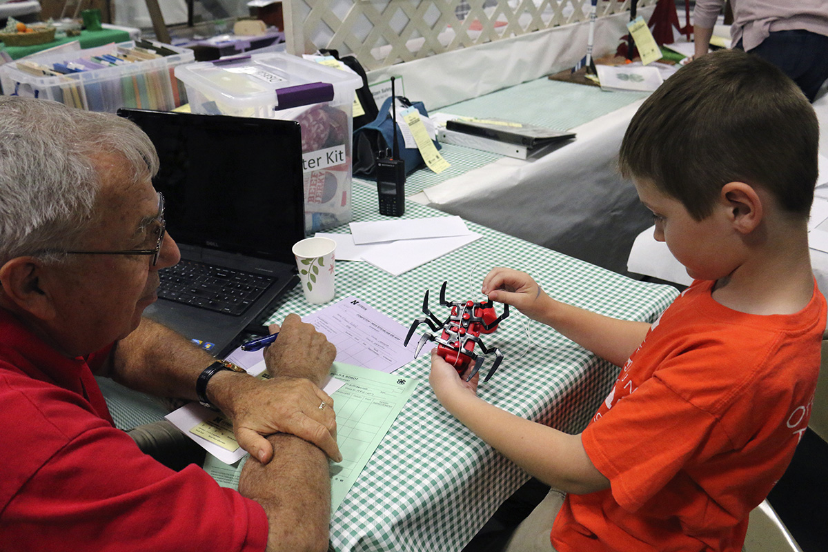 Pictured is a youth discussing his kit-labeled robot with a judge.