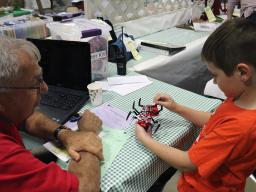 Pictured is youth discussing his kit-labeled robot with a judge.
