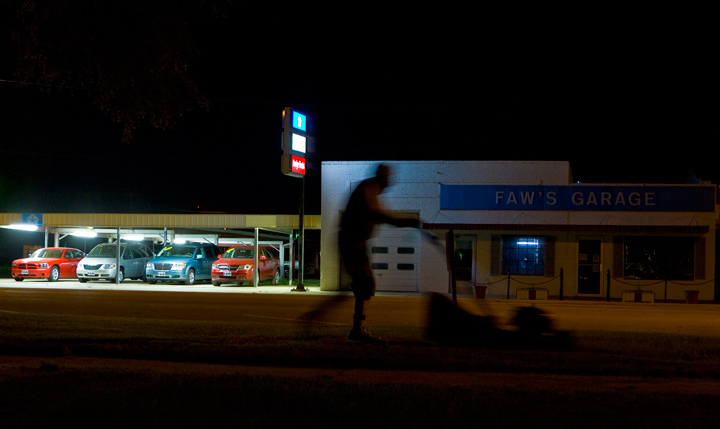 "A man mows the lawn across the street from Faw's Garage in Arapahoe, Neb., in this photo from the ""Real Nebraska"" series."