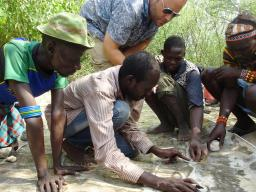 Matthew Douglass, assistant professor of practice in the College of Agricultural Sciences and Natural Resources, (standing) works with Daasanach men to mark out pasture boundaries, watering points and conflict areas on prints of satellite imagery.   Court