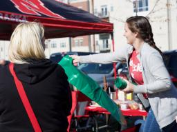 Natalie Bielenberg, a volunteer with Go Green for Big Red, hands out green recycling bags at a football tailgate Oct. 26.