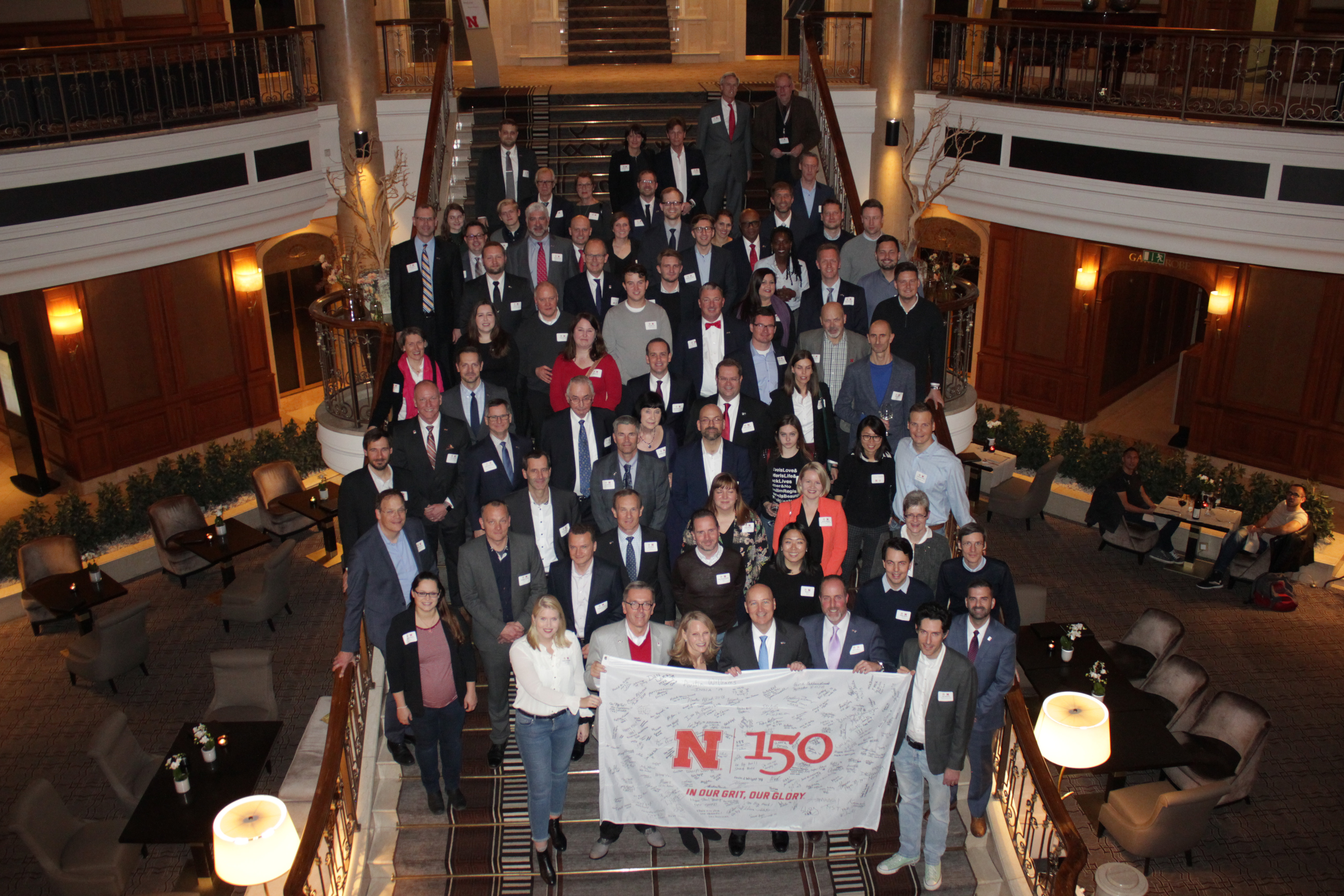 Participants from the Friends and Alumni Reception in Berlin, Germany on November 11 stand with the N150 flag in honor of UNL's 150th anniversary.