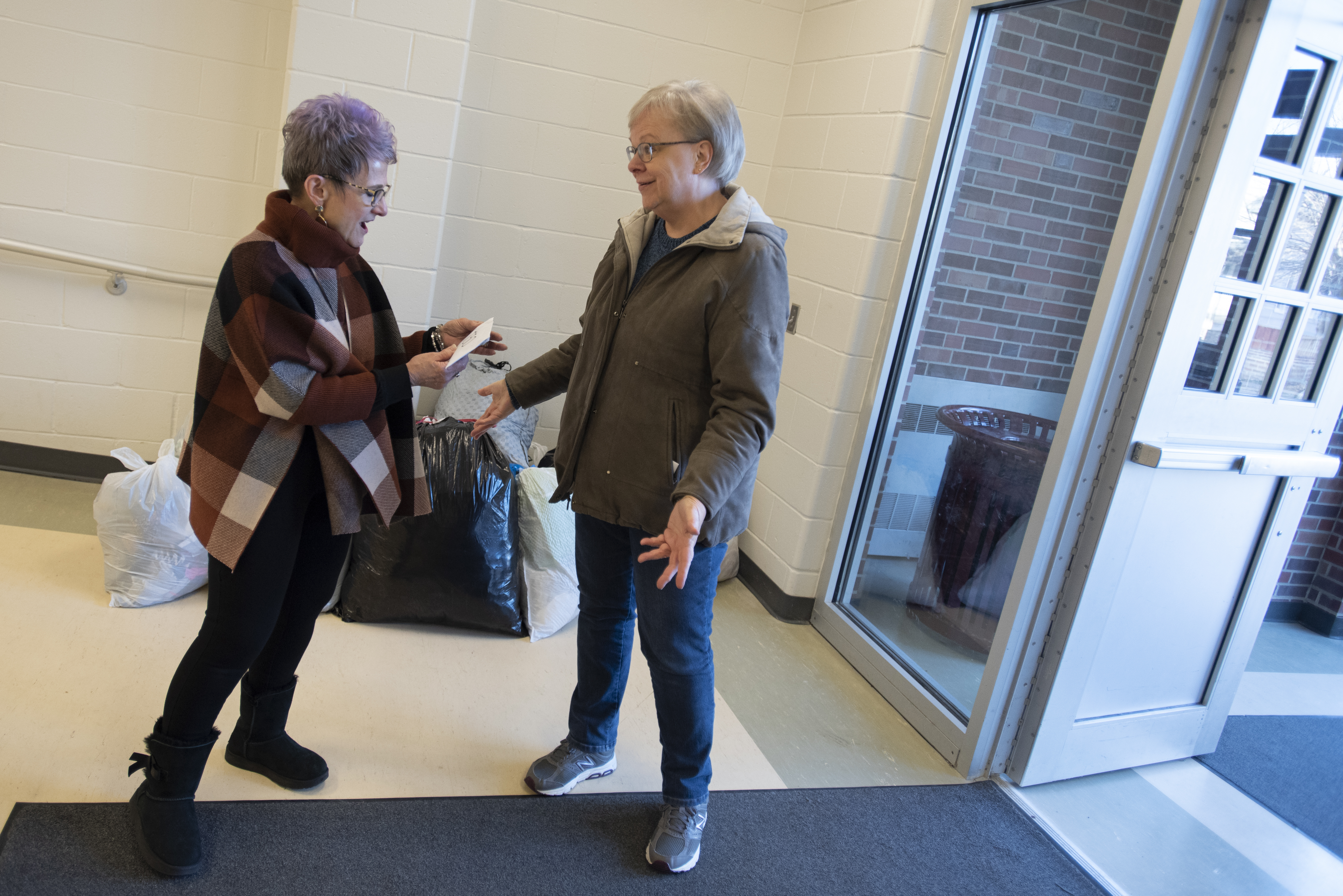 Dee Ebbeka hands Linda Kern, of Clinton Elementary School, the last of the Caring for Clinton donations Dec. 6, 2019, at the school on Holdrege Street. | Shawna Richter-Ryerson, Natural Resources