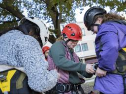 Alaina Kapla, UNL Forestry Club president, helps high school students get on their tree climbing gear during a summer climbing session at Hardin Hall. | Shawna Richter-Ryerson