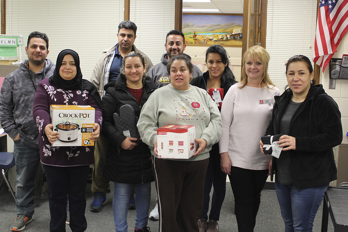 NEP staff member Dana Hardy (second from right) with an English Language Learner class after they received cookware items.