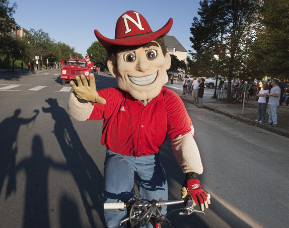 Herbie Husker pedals through UNL's 2010 homecoming parade.