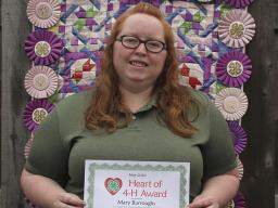 Pictured behind Mary is her senior year 4-H project, a quilt made of all her 4-H ribbons.