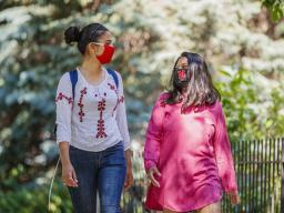 Asmita Jayswal, a junior in computer science (lright), and Esha Mishra, a graduate student in physics, walk along R Street wearing the new N face mask. More than 60,000 face masks will be distributed to all students, faculty and staff for the fall semeste