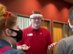 David Strang, an events associate with Academic Services and Enrollment Management, wears a face shield from Nebraska Innovation Campus while visiting with fellow Huskers. The face shields will be distributed to offices and colleges across campus to suppo