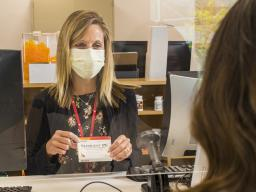 Student selects over-the-counter medicine at the University Health Center pharmacy.