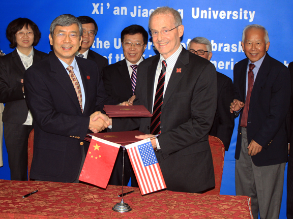 Chancellor Harvey Perlman (front, right) shakes hands with Zheng Nanning, president of Xi'an Jiaotong University, after signing the agreement to create an American Culture Center in China.