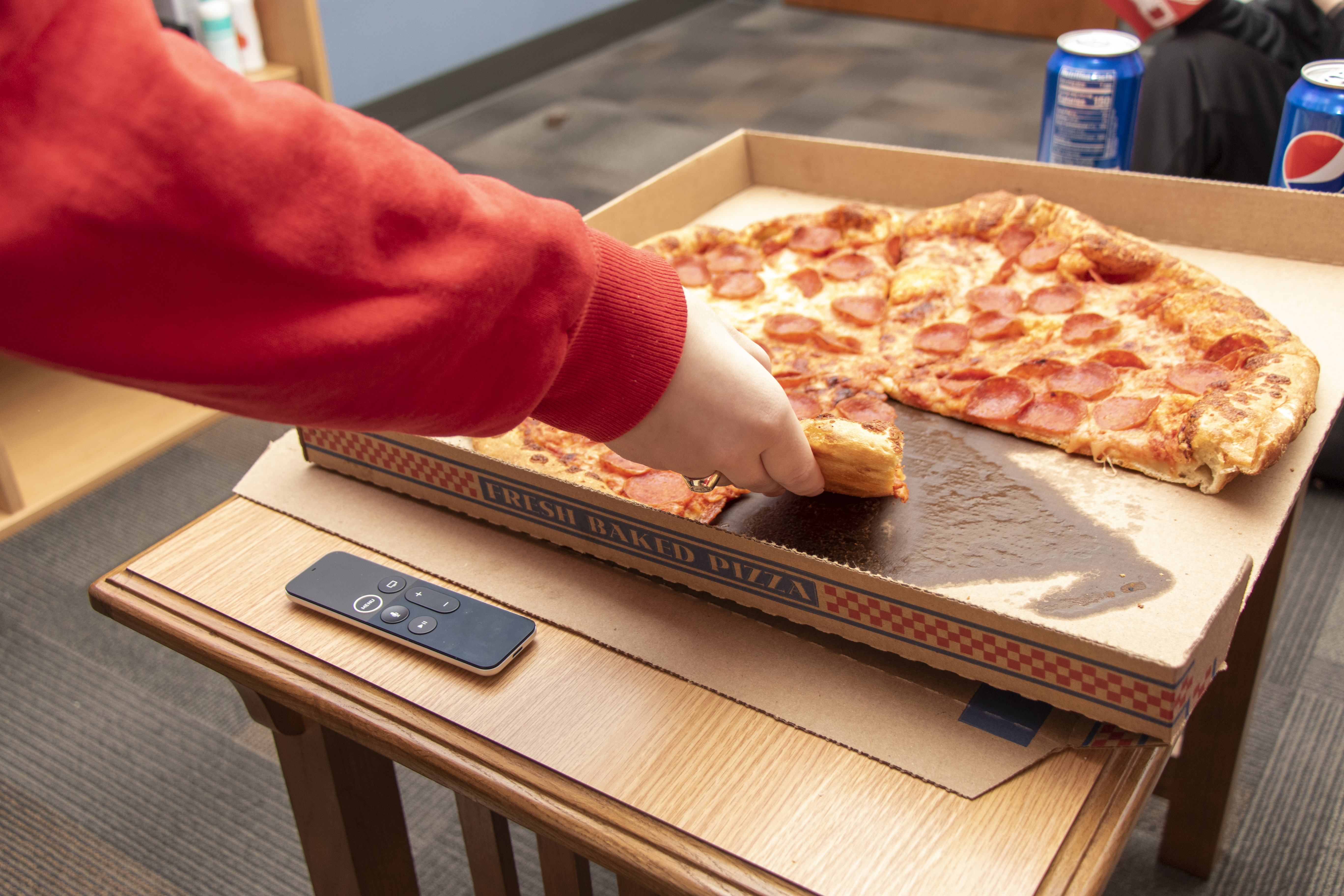 A student grabs a slice of pizza from a pizza box.