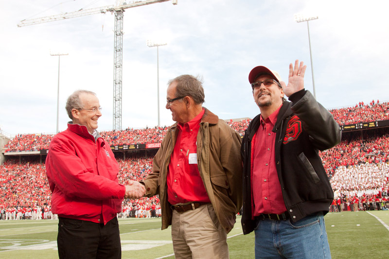 Chancellor Harvey Perlman shakes hands with Jeff Sotzing as Larry Witzer waves to the crowd during a second quarter time out at the Nov. 5 Husker football game. Sotzing and Witzer are with the John W. Carson Foundation. Photo by Craig Chandler|UComm