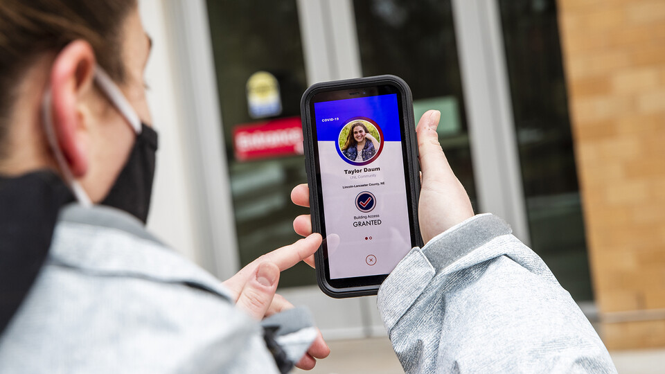 Taylor Daum demonstrates the Safer Community app, which will be used as part of the university's COVID-19 testing plans in the spring semester. Screen is simulated and may change slightly when the app is finalized.