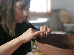Rhonda Willers pinching the rim of a basin form made of earthenware. Photo by April Bodenburg.
