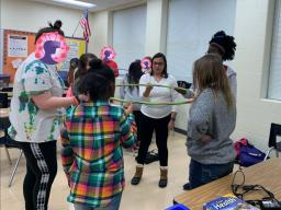 NE STEM 4U mentor Amy Klar and participants use a hula hoop to experiment with network interdependence.