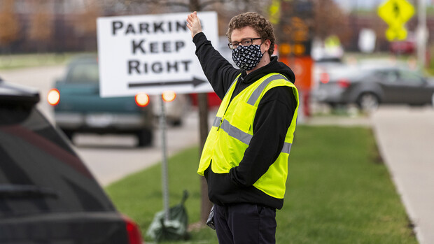 Noah Schwendeman directs traffic along Pinnacle Arena Drive as people arrive for their vaccine on April 7. Schwendeman said he volunteered for the clinic to help the community edge toward a return to normal. [ Craig Chandler   University Communication ]