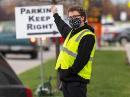 Noah Schwendeman directs traffic along Pinnacle Arena Drive as people arrive for their vaccine on April 7. Schwendeman said he volunteered for the clinic to help the community edge toward a return to normal. [ Craig Chandler | University Communication ]