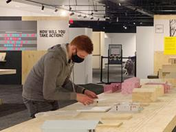 """A student sets up the """"NEw Attainable House"""" exhibition at the Nebraska History Museum."""