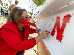 Sheri Jones, dean of the College of Education and Human Sciences, signs the final beam that was lifted into place during the April 9 topping out ceremony. An evergreen tree was also placed atop the beam, signifying the safe completion of the internal stru