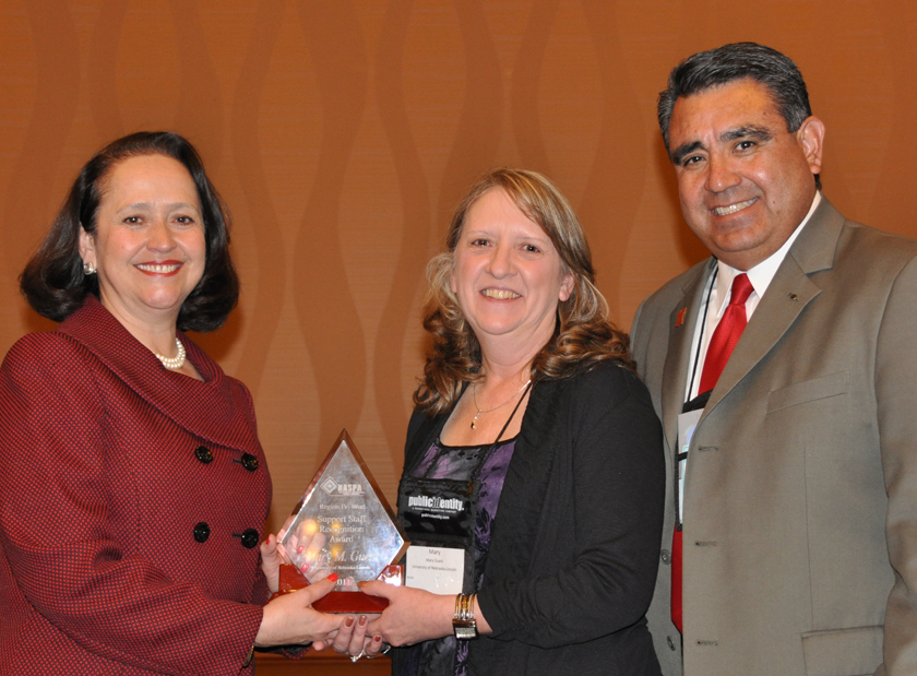 UNL's Mary Guest (center) receives the NASPA award from Patricia Telles-Irvin, NASPA president, and Timothy Alvarez, UNL's assistant vice chancellor for student affairs.