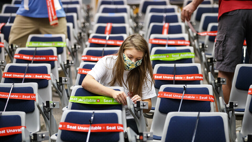 Maddie Huppert, a student worker in the Office of the Executive Vice Chancellor, wraps a green band on an available seat in a Louise Pound Hall lecture space in August 2020.