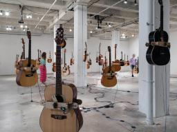 """Guitars hang in the air as patrons examine the """"Soundtracks for the Present Future"""" exhibition in Omaha's Bemis Center for Contemporary Arts. Courtesy photo."""