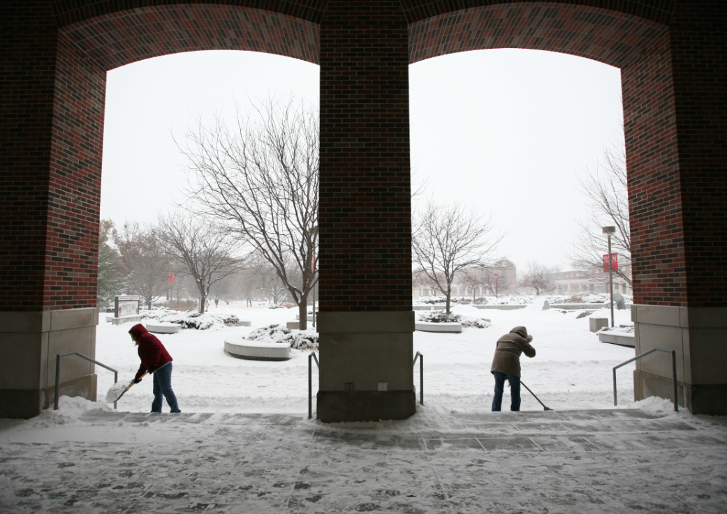 UNL employees scoop snow outside the Nebraksa Union.