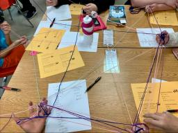 Youth discover connections to each other by creating a network model of shared interests out of yarn.