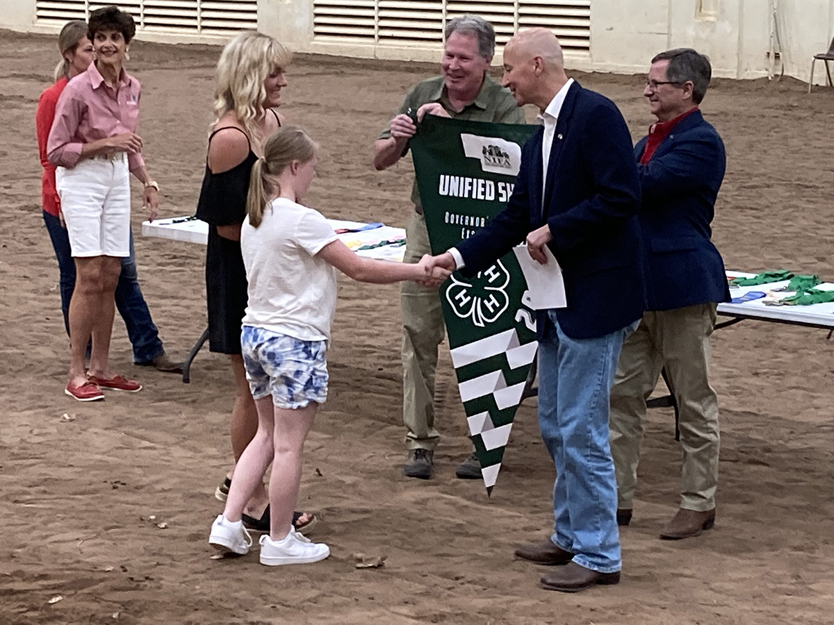 Governor Pete Ricketts shakes hands with a member of the Unified Showing 4-H club.