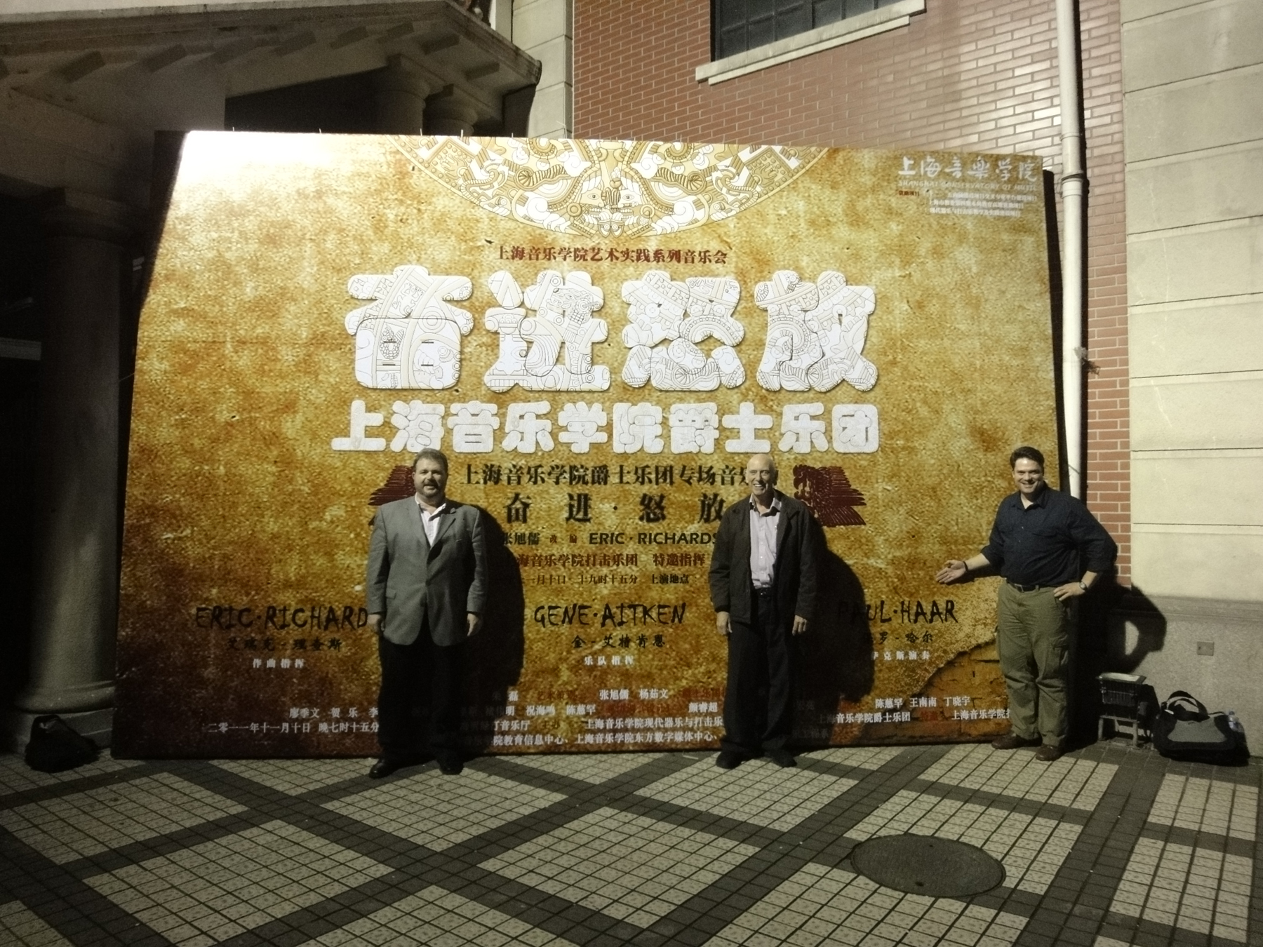 (From left) Eric Richards, Gene Aitken and Paul Haar stand next to a poster advertising the Shanghai Conservatory Jazz Orchesta's concert featuring the commissioned work of Richards with guest soloist Haar.