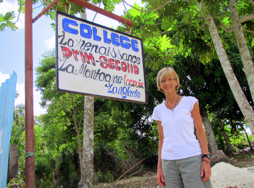 Susan Sheridan, director of the Nebraska Center for Research on Children, Youth, Families and Schools, stands in front of a sign during her two-week mission trip to Haiti. During the trip, Sheridan studied the educational system in the rural region of La