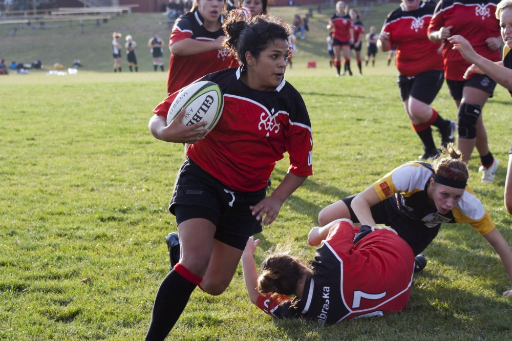 Senior scrumhalf, Bryana Delira breaks through a tackle to run the ball against the Wayne State Wildcats