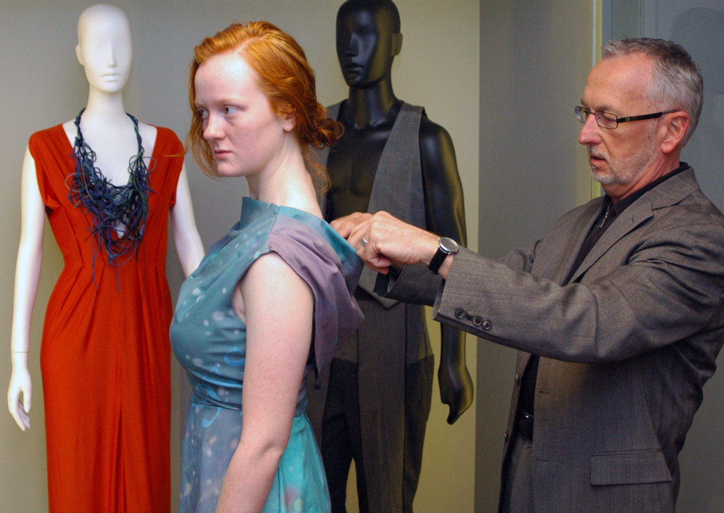 "Michael James makes adjustments to a ""text analysis"" dress worn by Kate Rask. The dress, which will be featured in the April 20 fashion show, was designed by Kendra Morgan."