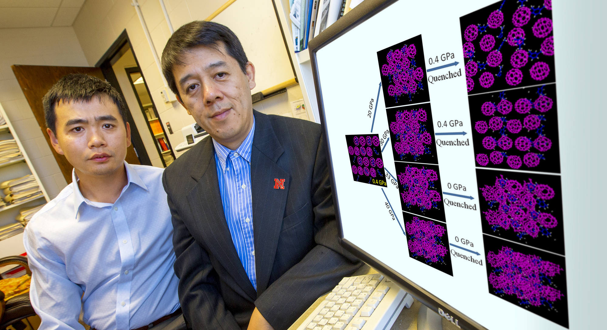 Xiao Cheng Zeng (right) and postdoctoral researcher Hui Li with their computer-generated images of what happens to buckyballs (pink) when they're infused with molecules of the C8H10 solvent (blue), then crushed by intense pressure and released.