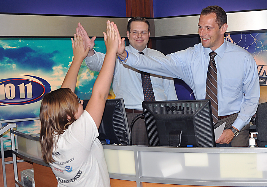 A 2012 Weather Camp participant gets a few high-fives from the KOLN news team during a visit there in June.