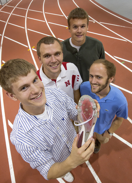 Alex Adams (left), Shawn Bernard, Tommy Brinn and Walter Bircher of Blue Inventor LLC gather at UNL's indoor track with their product, TiteSpike, in place on the track shoe. (photo: Craig Chandler, University Communications)