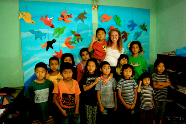 Hannah Potter (center) is surrounded by the children at the One Way Children's Home in Nepal in front of their mural.