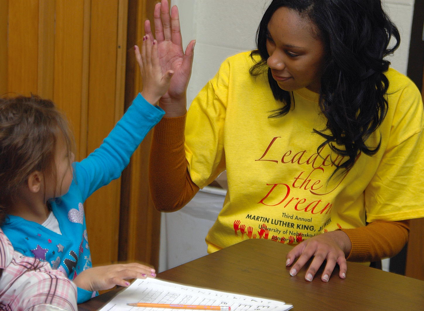 UNL student Rhaniece Choice offers a high five to an elementary school student during an Martin Luther King Jr. outreach event earlier this year.